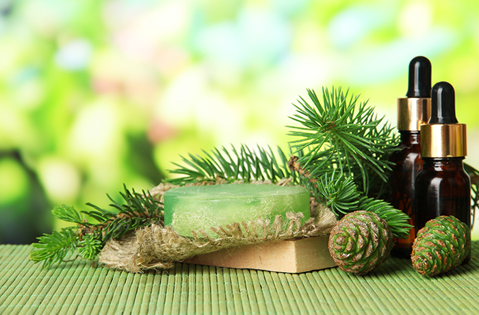 Hand-made soap and bottles of fir tree oil on bamboo mat